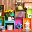 Beautiful colorful shelves with different home related objects on wooden wall background — Stock Photo #61088993