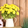 Flowers in vase on wooden wall background — Stock Photo #61089093