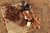 Pile of coffee beans with chocolate, nuts and cinnamon on burlap cloth on wicker mat — Stock Photo
