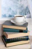 Books and cup on the windowsill — Stock Photo