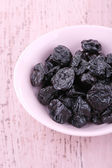 Bowl of prunes on color wooden background — Stock Photo
