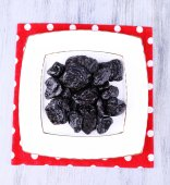 Squared white plate of prunes — Stock Photo