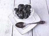 Glass bowl of prunes on white plate with spoon on color wooden background — Stock Photo