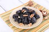 Plate of prunes and walnuts — Stock Photo