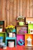 Beautiful colorful shelves with different home related objects on wooden wall background — Stock Photo