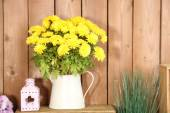 Flowers in vase on wooden wall background — Stock Photo