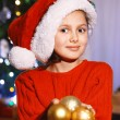 Cute little girl in Santa hat decorating Christmas tree — Stock Photo #61092119