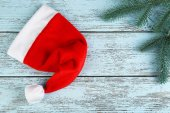 Santa red hat with fir-tree on color wooden background — Stock Photo