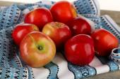 Heap of apples with dishcloth on wooden table background — Stock Photo
