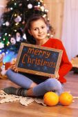 Cute little girl with greeting Merry Christmas — Stock Photo