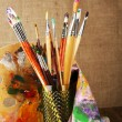 Paint brushes with paints and palette on beige background — Stock Photo #61127083