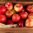 Red apples in wooden crate with burlap cloth — Stock Photo #61128405