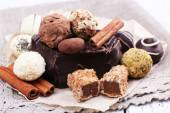 Pile of chunk of chocolate and truffles with cinnamon stick on crumbled paper, grey material and wooden background — Stockfoto