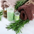 Branches of rosemary, towels and bottle with massage oil and sea salt on color wooden background. Rosemary spa concept — Stock Photo #61210169