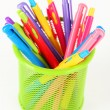 Colorful pens in green metal vase isolated on white background — Stock Photo #61210189