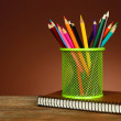 Colorful pencils in green metal holder with notebook on wooden table and shaded color background — Stock Photo #61210285