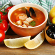Tasty soup with shrimps, mussels, tomatoes and black olives in bowl on wooden background — Stock Photo #61215353