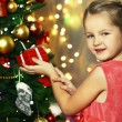 Little girl decorating Christmas tree on bright background — Stock Photo #61218001