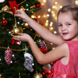 Little girl decorating Christmas tree on bright background — Stock Photo #61218009
