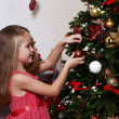 Little girl decorating Christmas tree on bright background — Stock Photo #61218087