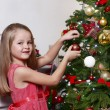 Little girl decorating Christmas tree on bright background — Stock Photo #61218093