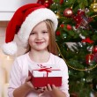 Little girl in Santa hat holding present box near Christmas tree on light background — Stock Photo #61218183