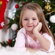 Little girl lying on fur carpet on Christmas tree background — Stok fotoğraf #61218243