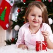 Little girl lying with gift on fur carpet on Christmas tree background — Stok fotoğraf #61218257