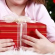 Little girl lying with gift on fur carpet on Christmas tree background — Stock Photo #61218271