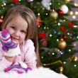 Little girl with mittens lying on fur carpet on Christmas tree background — Stock Photo #61218273