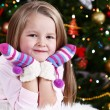 Little girl with mittens lying on fur carpet on Christmas tree background — Stok fotoğraf #61218277