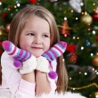 Little girl with mittens lying on fur carpet on Christmas tree background — Stok fotoğraf #61218287