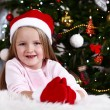 Little girl in Santa hat and mittens lying on fur carpet on Christmas tree background — Stock Photo #61218301