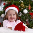 Little girl in Santa hat and mittens lying on fur carpet on Christmas tree background — Stok fotoğraf #61218307