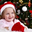 Little girl in Santa hat and mittens lying on fur carpet on Christmas tree background — Stok fotoğraf #61218309