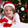 Little girl in Santa hat and mittens lying on fur carpet on Christmas tree background — Stock Photo #61218313