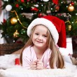 Little girl in Santa hat lying on fur carpet on Christmas tree background — Stok fotoğraf #61218361