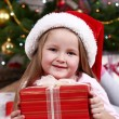 Little girl in Santa hat lying on fur carpet on Christmas tree background — Stock Photo #61218363