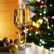 Two glass with champagne with chocolates and baubles on table on Christmas tree and fireplace background — Stock Photo #61218439