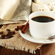 Cup of coffee with coffee beans and cinnamon on burlap cloth on wooden table background — Stock Photo #61218549