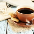 Cup of coffee with spoon and cookies on burlap cloth near envelopes on color wooden background — Stock Photo #61218623