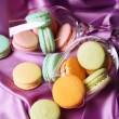Gentle colorful macaroons in wine glass on color fabric background — Fotografia Stock  #61219107