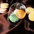 Gentle colorful macaroons in wine glass on color fabric background — Fotografia Stock  #61219141