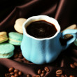Gentle colorful macaroons and black coffee in mug on color fabric background — Fotografia Stock  #61219237