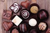 Many chocolates on wooden textured background — Stock Photo