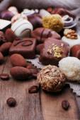 Different chocolates with coffee beans on grey fabric on wooden background — Stock Photo