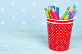 Plastic cup with different pens on color wooden table on color wooden table and blue background with printed stars — Stock Photo