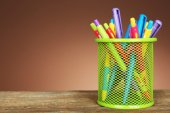 Colorful pens in green metal holder on wooden table and shaded color background — Stock Photo