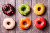 Delicious donuts with glaze on wooden background — Stock Photo