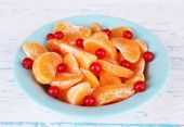 Bowl of slices mandarin with currants on color wooden surface on white background — Stock Photo
